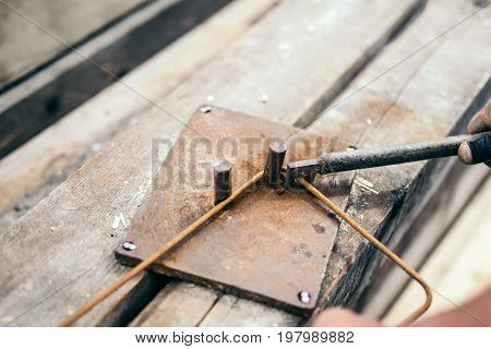 Worker Hands Using Steel Wire And Pincers To Bend Steel Bars, Preparing For Concrete Pouring On Cons