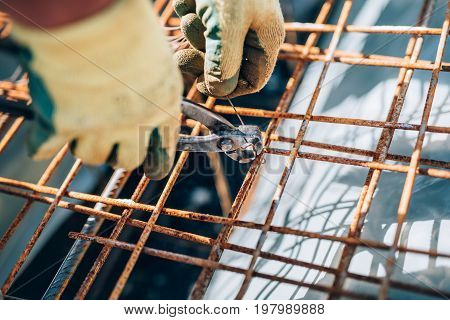 Details Of Steel Reinforcement On Construction Site. Industrial Construction Worker Using Pliers And