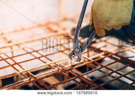 Hands Of Construction Worker Using Pliers And Securing Steel Bars With Wire Rod For Reinforcement Of