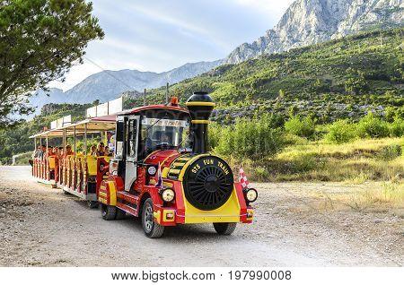 Sightseeing bus on the embankment Makarska.- JUNE 1: Sightseeing bus on the waterfront Makarska on the background of mountains and pine trees, June 1, 2017. Croatia.