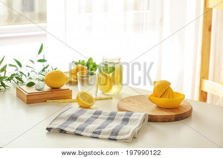 Cutting board with squeezer, lemons, glass and jar of lemonade on table in light room