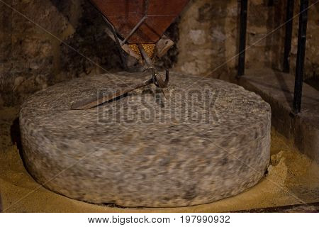 heavy old rotating millstone in watter mill