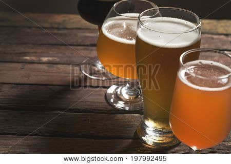 Detail of pale dark unfiltered pale and red fruit beer in four different beer glasses on a rustic wooden table. Selective focus on the third glass