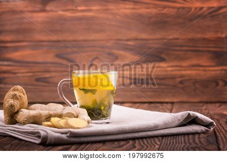 A close-up of a tea cup full of yellow beverage on a dark wooden background. A cup of beverage with cut lemon, ginger and green tea leaves on a gray table-cloth. Autumn healthful tea. Copy space.