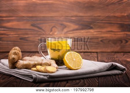 A close-up of a glass cup full of green tea on a wooden background. A cup of hot beverage, ginger root and sour cut lemon on a fabric table cloth. Winter organic beverage. Healthy tea. Copy space.