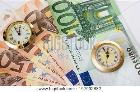 European banknotes like background and two clocks that have five to twelve time. Highest time for action.