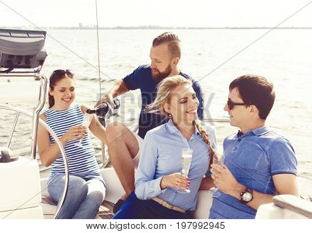 Group of friends traveling on a yacht, enjoying a good summer day and drinking champagne. Vacation, holiday and summertime concept.