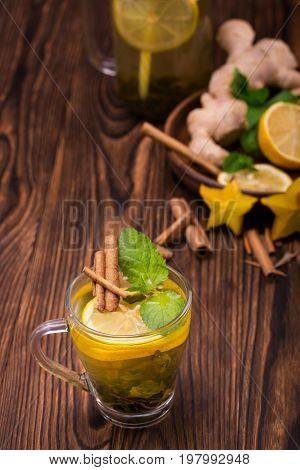 A close-up of a glass cup full of green tea on a dark wooden background. A cup of hot yellow beverage with lemon, cinnamon and mint. Autumn organic beverage. Healthful herbal tea. Copy space.