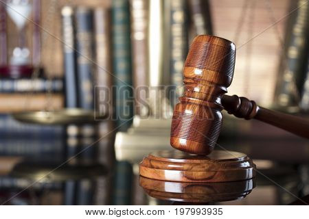 Law theme - court library. Gavel of the jugde and scale of justice in the court library. Wooden background.