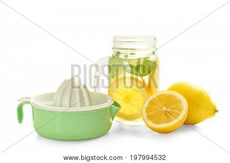 Plastic squeezer, fresh lemons and jar with lemonade on white background