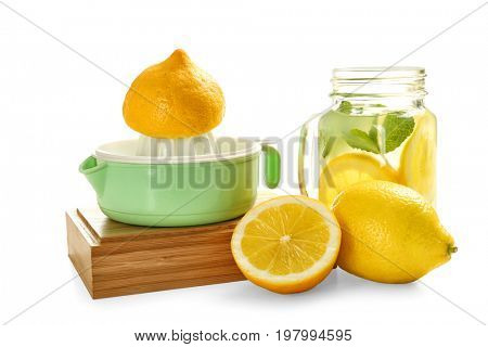 Wooden box with squeezer, lemons and jar of lemonade on white background