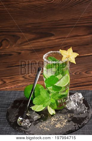 Summer bright mojito cocktail from mint, limes, rum and ice cubes on a dark wooden background. An alcoholic beverage with fresh lime segments, brown sugar, ice, mint leaves and decorative carambola.