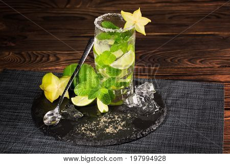 A beautiful green mojito cocktail from mint, limes, rum and ice cubes on a dark wooden background. An alcohol beverage with decorative carambola, brown sugar, ice cubes and mint leaves. Alcohol drink.