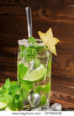 Close-up of a glass full of alcohol cocktail from juicy lime, rum, fresh mint, decorative carambola and crushed ice on a wooden background. Summer refreshing beverage in highball glass with spoon.