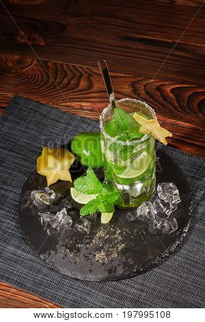 Top view of a glass full of alcohol cocktail from juicy lime, rum, fresh mint, decorative carambola and crushed ice on a dark wooden background. Summer non-alcohol mojito.