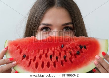 The girl hid behind a slice of fresh watermelon and only her eyes are visible. The brunette is dressed in a black jersey. The girl stands on a light background.