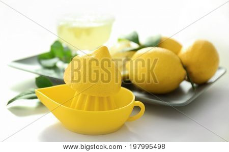 Squeezer with half of lemon on white background