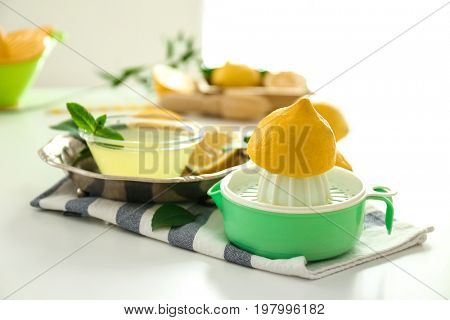 Composition with squeezer, lemons and juice on white table