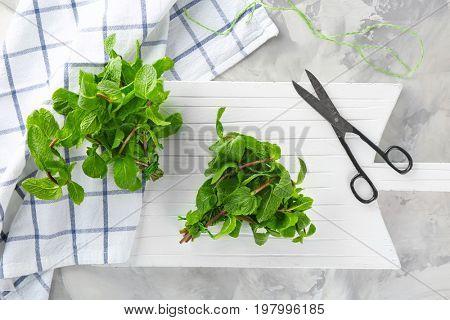 Lemon balm with scissors on wooden board