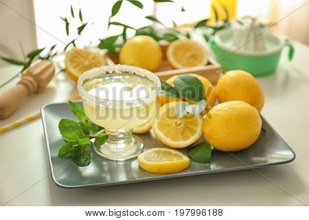 Platter with glass of juice and lemons on white table