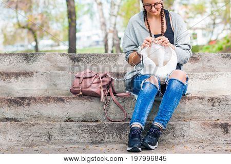 Young Woman  Knits With Knitting Needles