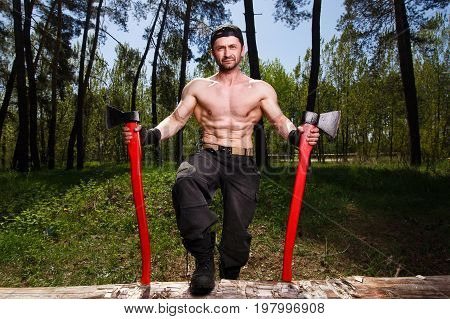 Lumberjack Worker Standing In The Forest With Two Big Axes
