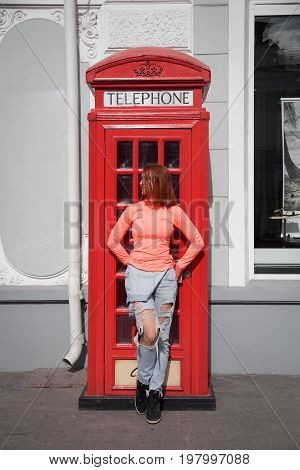 A young beautiful woman with red hair in ragged jeans and an orange jacket is standing in the street next to a red phone booth in London style