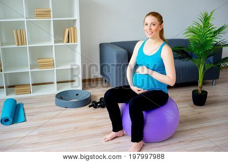 Pregnant woman doing pre-natal exercises at home