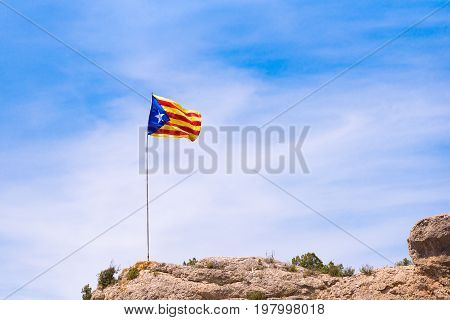 The Spanish flag (Estelada) on the mountain over blue sky background Catalunya Spain. Copy space for text