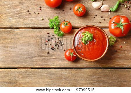 Bowl with sauce, tomatoes, greenery and spices on wooden table