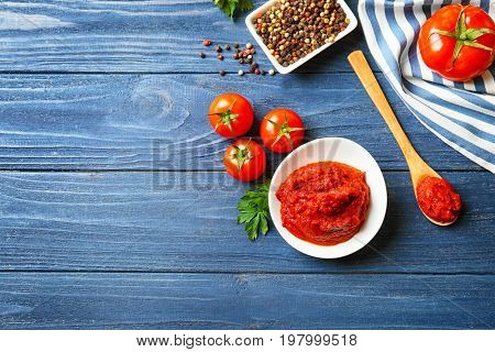 Ceramic bowl with sauce, spoon, tomatoes and spices on wooden table