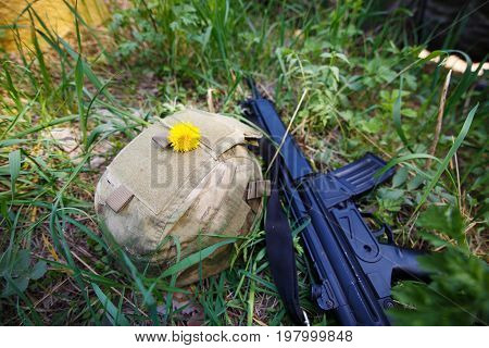 Military helmet rifle and a flower in the grass close up. Soldier military mercenary stop war paintball concept poster