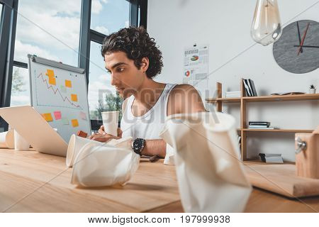 Hardworking Businessman In Underwear With Disposable Cup Of Coffee In Hand Typing On Laptop At Workp