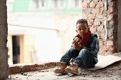 Cute little boy sitting on floor with piece of bread in abandoned building. Poverty concept poster