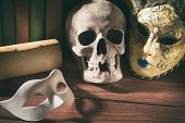 Theater and drama concept. Human skull venetian masks with old scroll and books on wooden table. poster