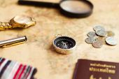 Compass on vintage world map with coins, pen, Magnifying glass and scarf for vacation and travel concept, selective focus.vintage style. poster