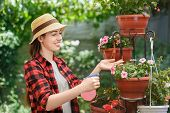 portrait of happy young woman gardener spraying water on flowers. Girl with sprayer bottle spraying pesticide. People, gardening, care of plants, hobby concept poster