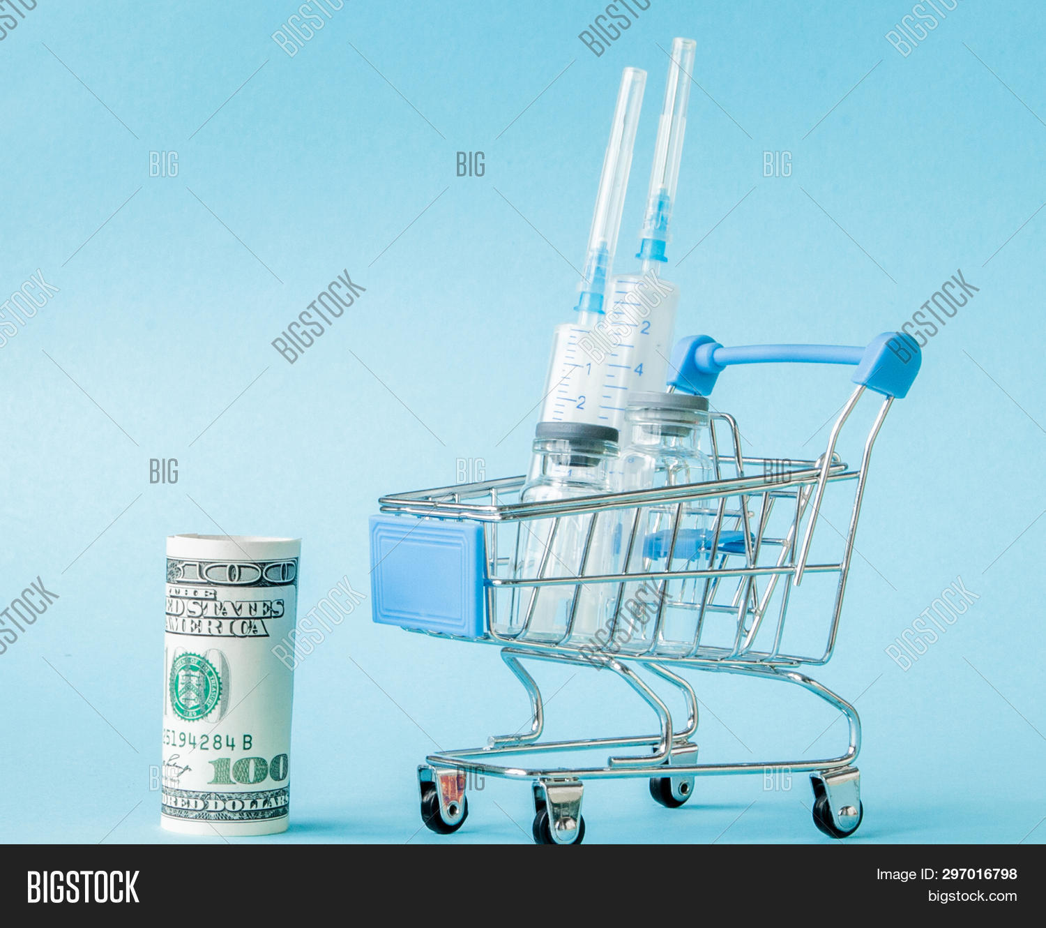 Medical Injection And Dollars In Shopping Trolley On Blue Background. Creative Idea For Health Care