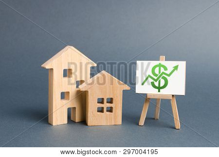 Wooden Figures Of Houses And A Poster With Green Arrow Up. The Concept Of Real Estate Value Growth.
