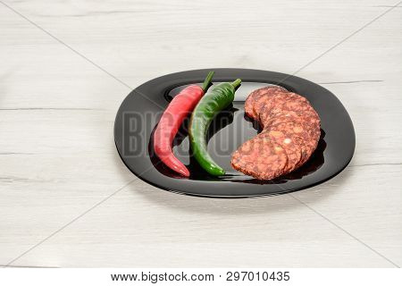 Pepper Salami In Slices With Red And Green Chilli Fresh Peppers Lie On Glossy Black Plate On A White