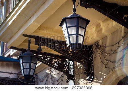 Iron Hanging Street Lamp Against The Background Of The Facade Of The Building In Yellow Color Close-