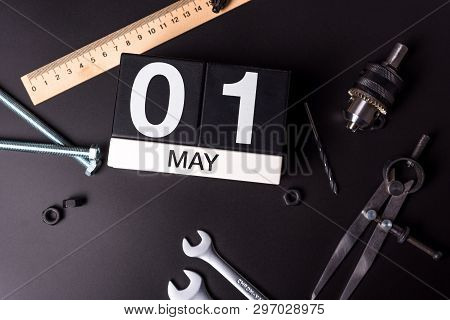Labour Day. May 1st. Day 1 Of May Month, Calendar On Black Background With Workers Tools