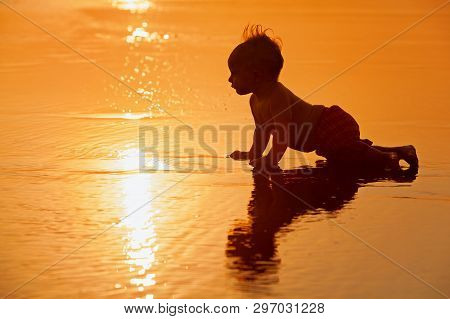 Black Silhouette Of Funny Baby Boy Crawling By Water Pool To Sea Surf For Swimming In Waves At Sunse