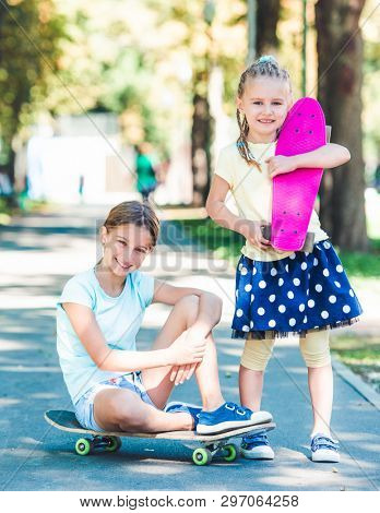 Smiling little girls with skateboards in the sunshine park