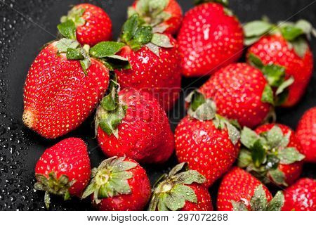 Fresh ripe strawberry with water drops on black background. Macro image.