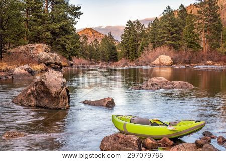 sunset over mountain river with an inflatable whitewater kayak - Poudre River below Mishiwaka, Colorado in early spring