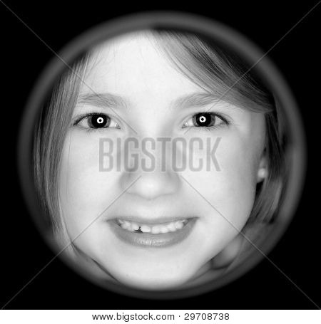 Little girl looking through hole with smile on face