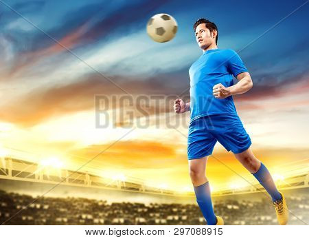 Asian Football Player Man Jump In The Air And Heading The Ball On Football Field At Stadium