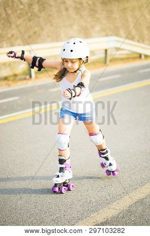 A Little Caucasian Girl With Roller Quad Rolling In The Sun Summer Evening. Rollerblading And Outdoo