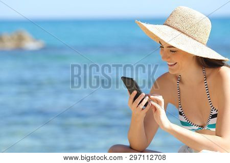 Happy Tourist Checking Smart Phone On A Beautiful Beach On Summer Vacation